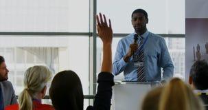 Altavoz masculino que obra recíprocamente con el público en un seminario 4k del negocio almacen de metraje de vídeo