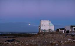 Altbau an der Küste von Sidi Kaouki, Marokko, Afrika Mond im Abendhimmel Langer Berührungsschuß Marokkos wonderfull Brandung zu lizenzfreie stockfotografie