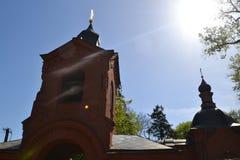 Altbau der Kirche mit einem Ziegelstein mit Kreuzen und der Helm auf dem Gebäude auf einem Hintergrund des blauen Himmels Lizenzfreies Stockbild