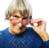 Alte ältere Dame, die durch ihre Brillen schaut Lizenzfreies Stockfoto