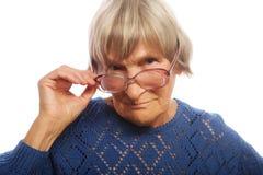 Alte ältere Dame, die durch ihre Brillen schaut Stockbilder