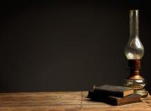 Alte Öllampe auf einem Holztisch nahe bei alten Büchern Stockfotografie