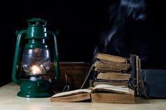 Alte Öllampe und -bücher, die auf dem Tisch liegen Eine Flamme von einem alten s Stockfoto
