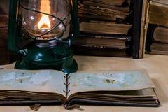 Alte Öllampe und -bücher, die auf dem Tisch liegen Eine Flamme von einem alten s Lizenzfreie Stockbilder
