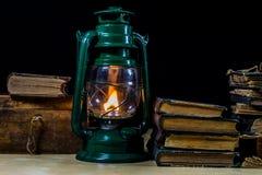 Alte Öllampe und -bücher, die auf dem Tisch liegen Eine Flamme von einem alten s Lizenzfreies Stockbild