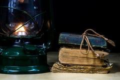 Alte Öllampe und -bücher, die auf dem Tisch liegen Eine Flamme von einem alten s Lizenzfreies Stockfoto