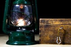 Alte Öllampe und -bücher, die auf dem Tisch liegen Eine Flamme von einem alten s Lizenzfreie Stockfotografie