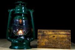 Alte Öllampe und -bücher, die auf dem Tisch liegen Eine Flamme von einem alten s Stockfotografie