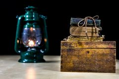 Alte Öllampe und -bücher, die auf dem Tisch liegen Eine Flamme von einem alten s Stockbilder
