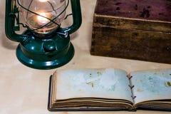 Alte Öllampe und -bücher, die auf dem Tisch liegen Eine Flamme von einem alten s Lizenzfreie Stockfotos