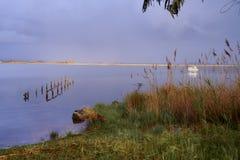 Alte Überreste des Docks und des weißen Bootes lizenzfreies stockbild