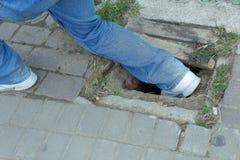 Alte Abdeckung des Unfallfußes die Entwässerung auf der Straße Lizenzfreies Stockfoto