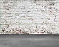 Alte abgestreifte Ziegelsteinwand mit schmutzigem konkretem Boden Stockbild