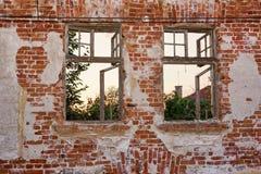 Alte abgezogene einsame Backsteinmauer mit dem Rahmen zwei zerbrochener Fensterscheiben Lizenzfreie Stockfotos