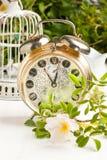 Alte Alarmuhr mit Blumen Stockfotos