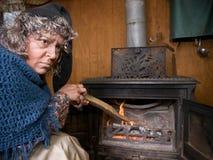 Alte alte Frau am hölzernen Ofen Stockbilder