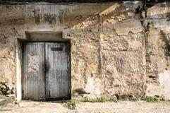 Alte alte Tür mit alter Schmutzbacksteinmauer Stockfotos