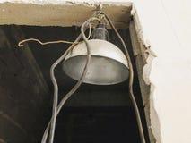 Alte Aluminiumlampe, verschoben auf einer Backsteinmauer in einem Neubau reparaturen Lizenzfreie Stockfotos