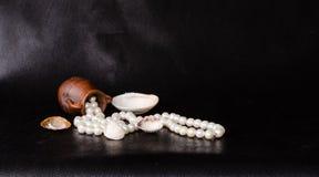 Alte Amphore, tropisches Seeoberteil und Perlen über Schwarzem Lizenzfreies Stockfoto