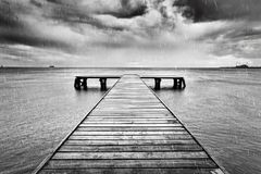 Alte Anlegestelle, Pier auf dem Meer Schwarzweiss, Regen Stockbild
