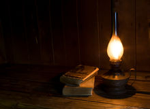 Alte antike Bücher mit brennender Paraffinlampe Stockfotografie
