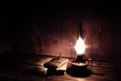 Alte Antike reserviert mit brennender Paraffinlampe nahe auf dem Holztisch Lizenzfreies Stockfoto