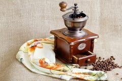 Alte antike seltene europäische Kaffeemühle, briet wohlriechende Kaffeebohnen und Schal auf rauem Hintergrund des Jutefasers stockbild