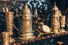Alte antike Weinleseteller, große silberne Becher, Uhren, selektiver Fokus Stockbild