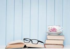 Alte antiquarische Bücher, Gläser und Porzellanschale auf dem Bücherregal Stockfoto