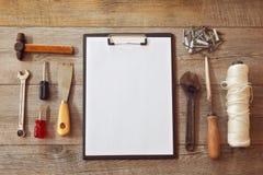 Alte Arbeitswerkzeuge auf hölzernem Hintergrund mit leerem Notizblock Ansicht von oben Lizenzfreie Stockfotos