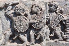 Alte Armee mit der Waffe, die das Kämpfen, Entlastung des hindischen Tempels hergestellt im 12. Jahrhundert anstrebt Indien Lizenzfreie Stockfotografie