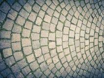 Alte Art der Straße pflasternd, gemacht von den Lavasteinquadraten, mit einer harmonisch halbkreisförmigen Struktur lizenzfreie stockfotos