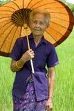 Alte Asiatin mit Sonnenschirm