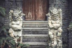 Alte asiatische Dämongottheiten am Eingebung zum alten Tempel mit alter Holztür und Steinschritten in Weinleseart Stockbild