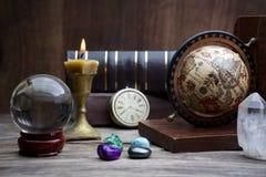 Alte Astrologie Alte Astrologiekugel und -bücher mit dem Beleuchten der Kerze Stockfotografie