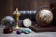 Alte Astrologie Alte Astrologiekugel und -bücher mit dem Beleuchten der Kerze Stockbild