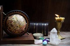 Alte Astrologie Alte Astrologiekugel und -bücher mit dem Beleuchten der Kerze Stockbilder
