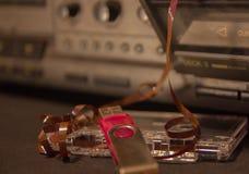 Alte Audiokassetten mit einem verwirrten Band, einem Kassettenrecorder und einem Blitz fahren Stockbild