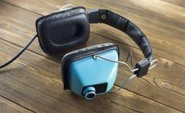 Alte Audiokopfhörer auf hölzernem hören stockfotos