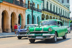 Alte Autos nahe bei traditionellen Gebäuden in altem Havan Stockfoto