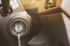 Alte Autoschlüssel nageln in das Schlüsselloch unter dem Lenkrad fest stockfoto