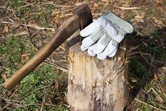 Alte Axt und alte Handschuhe auf einem Stumpf Lizenzfreie Stockfotos