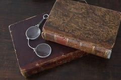 Alte Bücher angehäuft auf einem antiken Holzmöbel mit Lesebrille Stockfotos