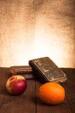 Alte Bücher, Apfel und orange Lügen auf einem alten Holztisch Stockbilder