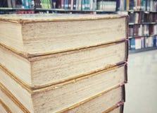 Alte Bücher auf altem Holztisch in der Bibliothek Stockfotos