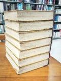 Alte Bücher auf altem Holztisch in der Bibliothek Lizenzfreies Stockfoto