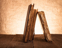 Alte Bücher auf altem Holztisch vor dem hintergrund der Leinwand Stockfoto