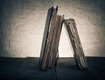 Alte Bücher auf altem Holztisch vor dem hintergrund der Leinwand Stockbilder