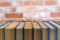 Alte Bücher auf Backsteinmauerhintergrund Stockfotos