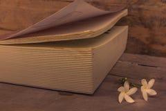 Alte Bücher auf Bretterboden mit den weißen Blumen gesetzt Stockfoto